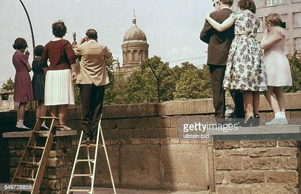 DEU DDR Berlin Menschen in Kreuzberg nähe HeinrichHeineStrasse schauen über die Berliner Mauer in Richtung Ostberlin hinten die Kirche St Michael im...