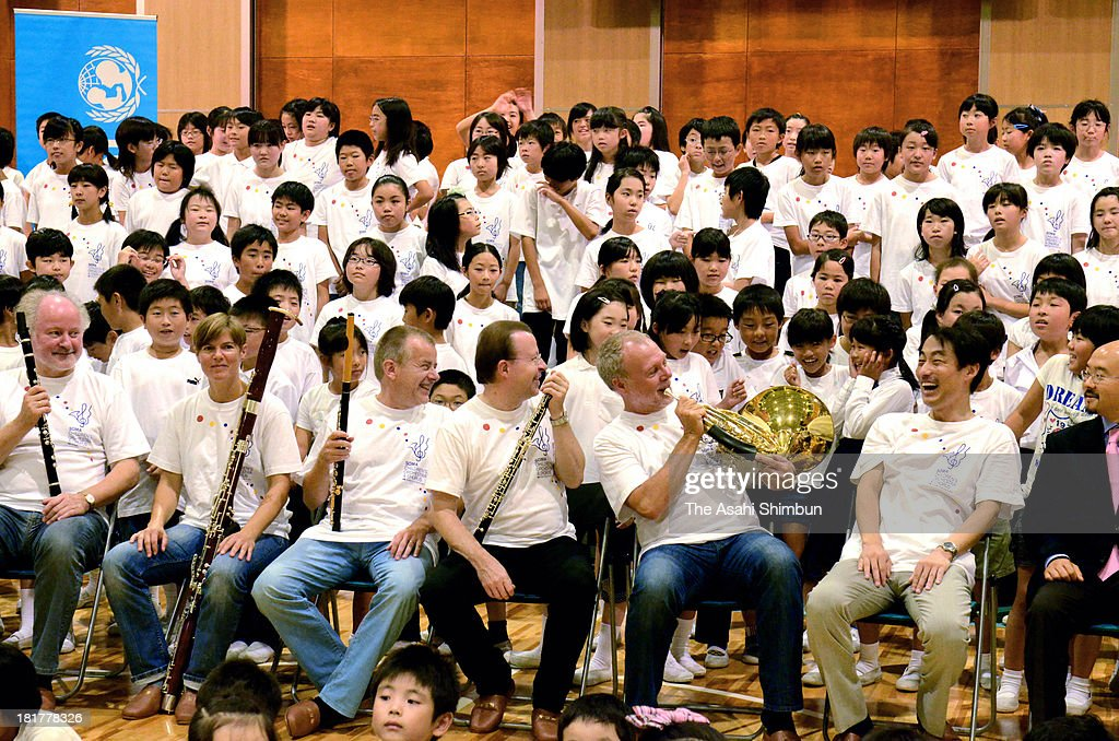 Berlin Philharmonic hornist Fergus McWilliam (3rd R) demonstrates his French horn for children on September 22, 2013 in Soma, Fukushima, Japan. The visit of the German musicians was part of support activities by El Sistema, an international music education group that provides instruments to children worldwide and dispatches music instructors.