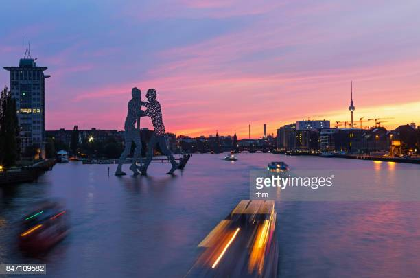 Berlin skyline -  sunset with the famous landmarks Molecule men, Oberbaumbrücke and Television-Tower with fast sightseeing boats (Kreuzberg-Friedrichshain, Berlin, Germany)