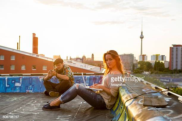 Berlin: young adults sitting on a roof, back lit