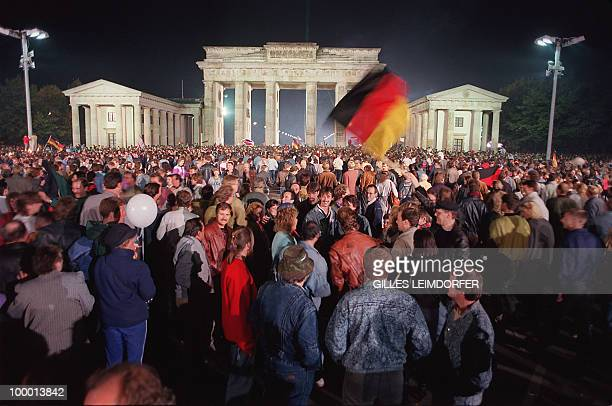 Berliner youths wave German flags as they celebrate the country's reunification at the Brandenburg Gate in Berlin 03 October 1990 Fortyfive years...