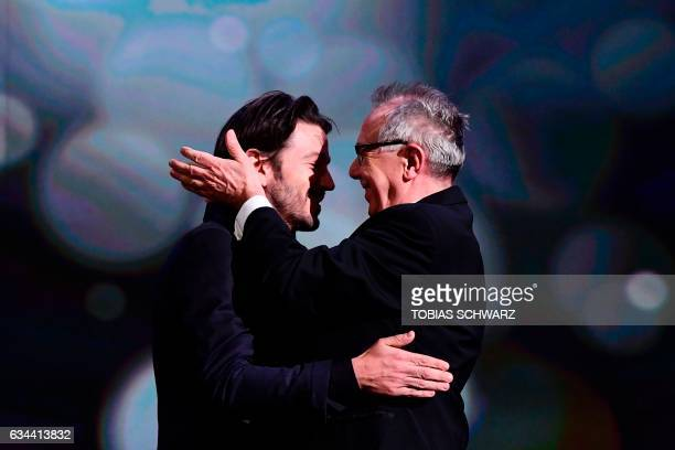 TOPSHOT Berlinale Director Dieter Kosslick and Member of the jury Mexican director Diego Luna embrace during the opening of the Berlinale film...
