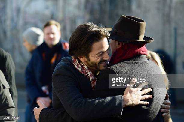 Berlinale director Dieter Kosslick greets actor Diego Luna in front of the Berlin wall in protest against barriers and walls in a simple gesture...