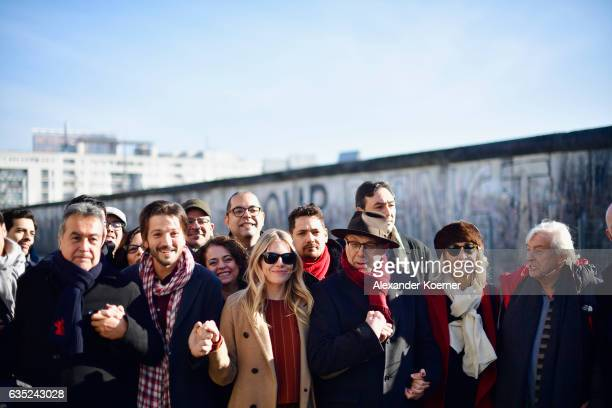 Berlinale director Dieter Kosslick poses with actor Diego Luna actress Sienna Miller and other jury members and delegates in front of the Berlin wall...