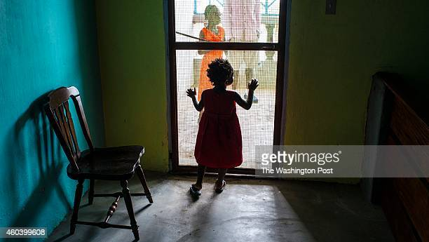 Berlinda stands at the screen door while others talk outside on Sunday September 21 2014 in Monrovia Liberia Berlina mother died of Ebola in an...
