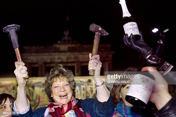 A berliner holds up a hammer and a chisel early on November 15 1989 in front of the wall at the Brandebourg Gate partly visible behind it as a crowd...