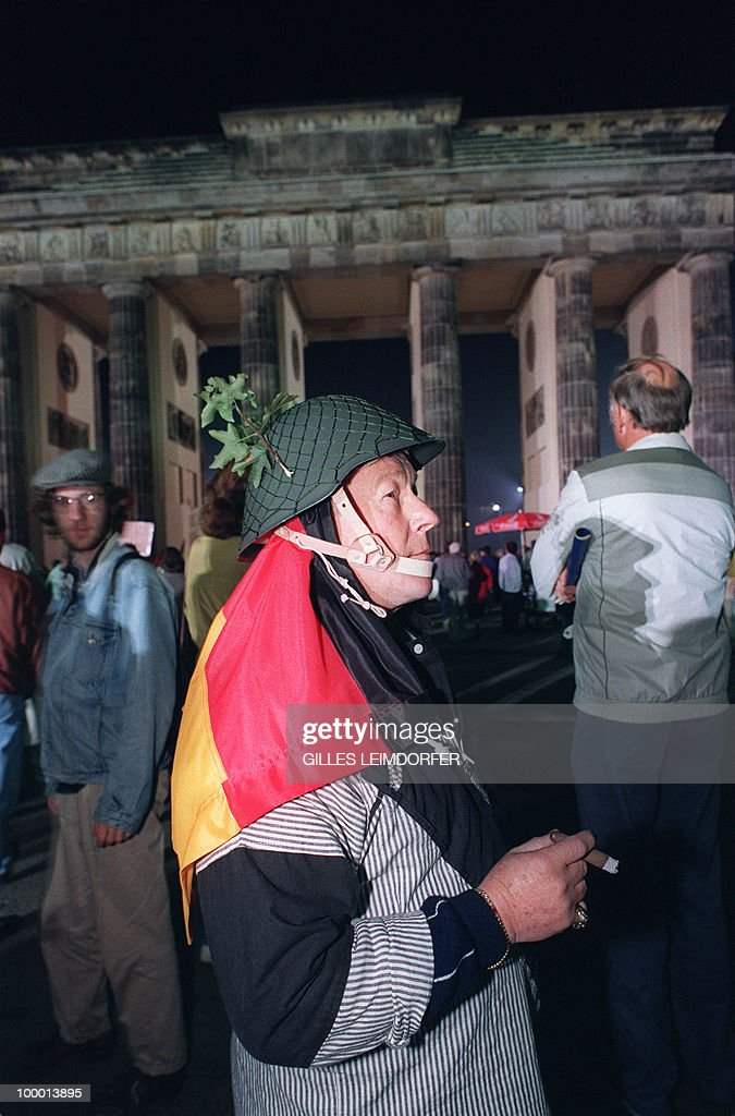 A Berliner, wearing an East German army helmet carrying a German flag on his shoulders, stands in front of the Brandenburg Gate in Berlin 03 October 1990 as he celebrates the country's reunification. Forty-five years after the end of the Second World War, Germany was free and united in liberty 03 October 1990, only 11 months since the Berlin Wall dividing East, German Democratic Republic and West, Federal Republic of Germany, began to disintegrate.