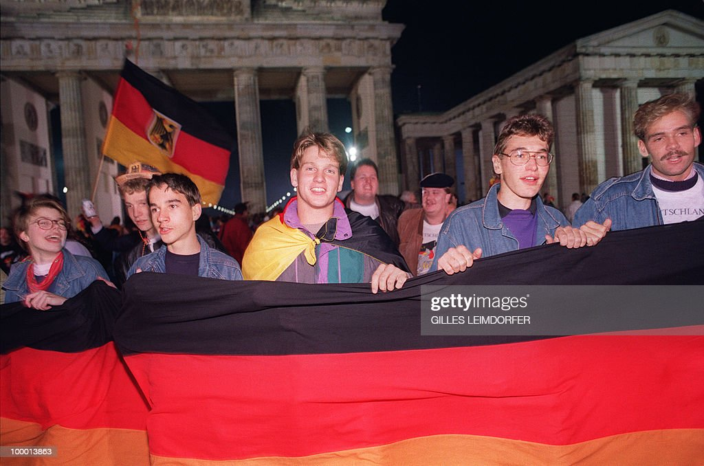 Berliner youths hold and wave German flags as they celebrate the country's reunification at the Brandenburg Gate in Berlin 03 October 1990. Forty-five years after the end of the Second War, Germany was free and united in liberty 03 October 1990, only 11 months since the Berlin Wall dividing East, German Democratic Republic and West, Federal Republic of Germany, began to disintegrate.