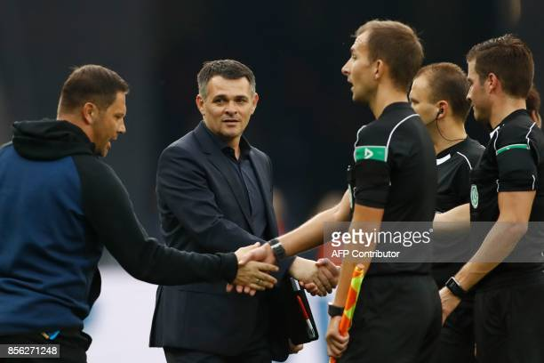 Berlin's Hungarian head coach Pal Dardai and Bayern Munich's French interim head coach Willy Sagnol shake hands with the officials after the German...