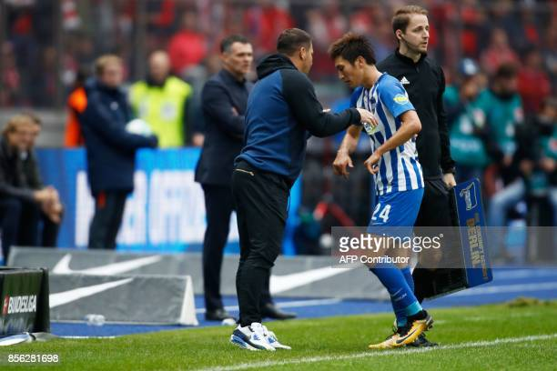 Berlin's Hungarian head coach Pal Dardai speak with Berlin's Japanese midfielder Genki Haraguchi as he comes off during the German first division...