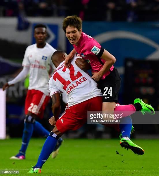 Berlin's Japanese midfielder Genki Haraguchi collides with Hamburg's Souza Walace during the German First division Bundesliga football match between...