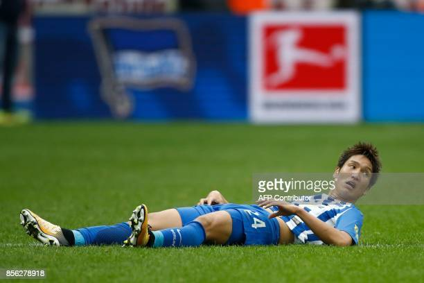 Berlin's Japanese midfielder Genki Haraguchi lays on the pitch during the German first division Bundesliga football match between Hertha Berlin and...