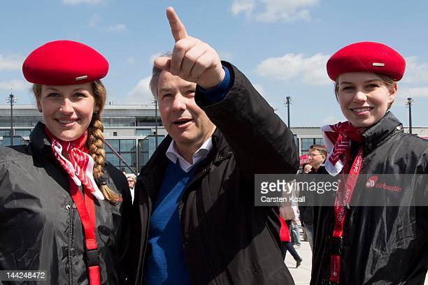 Berlin's major Klaus Wowereit gestures between two air hostesses of the airline Air Berlin at the open house weekend next to the construction site of...