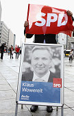 Berlin's Mayor and German Social Democrat Klaus Wowereit stands behind a SPD flag during an election campaign at Potsdamer Platz on August 1 2011 in...