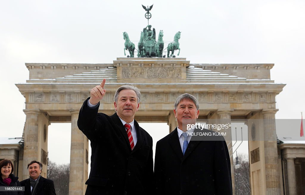 Berlin's mayor Klaus Wowereit (L) and Kyrgyz President Almazbek Atambayev stand in front of Berlin's landmark Brandenburg Gate on December 11, 2012. AFP PHOTO / WOLFGANG KUMM GERMANY OUT
