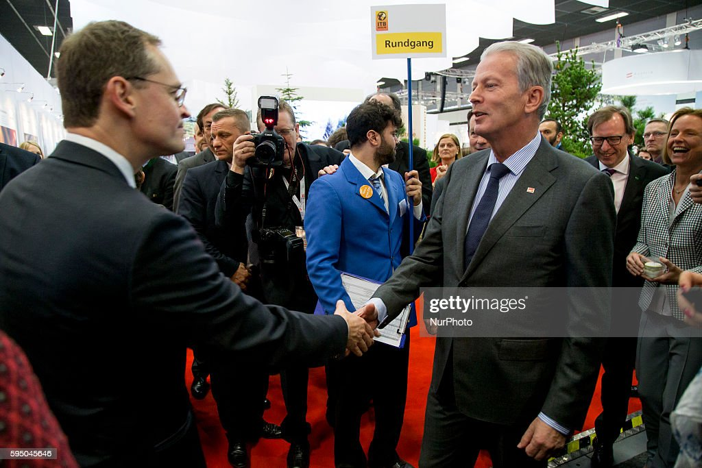 Berlin's Mayor Michael Mueller greets Austrian Vice Chancellor Reinhold Mitterlehner while visiting Austria's exhibition stand during an opening tour...
