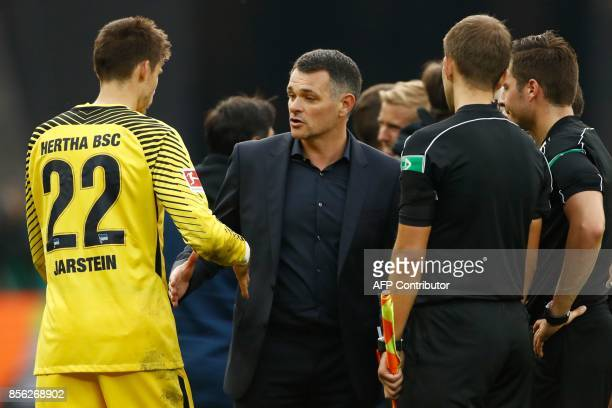 Berlin's Norwegian goalkeeper Rune Jarstein shakes hands with Bayern Munich's French interim head coach Willy Sagnol after the German first division...