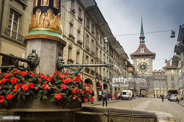 Bern city view with clock tower and red flowers.