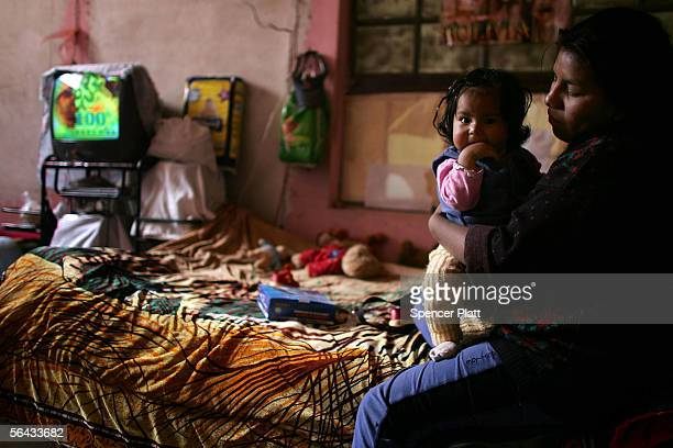Bernabe Chira the wife of a miner holds her child while sitting in her two room home that she shares with other members of her family outside of the...