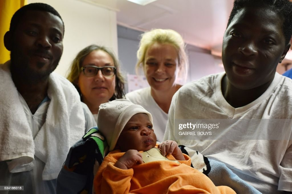 Bernadette Obiona and David Dibonde (L) pose with their newborn Alex during a family picture with Angelina Perri from Italy (2ndL), a nurse working for French NGO Medecins Sans Frontieres and doctor Erna Rijnierse (C) from Netherlands, on May 25, 2016 a day after a rescue of migrants off the Libyan coast. Alex is born today as the Aquarius is heading to the Sardinian port of Cagliari with 385 migrants on board. The Aquarius is a former North Atlantic fisheries protection ship now used by humanitarians SOS Mediterranee and Medecins Sans Frontieres (Doctors without Borders) which patrols to rescue migrants and refugees trying to reach Europe crossing the Mediterranean sea aboard rubber boats or old fishing boat. / AFP / GABRIEL