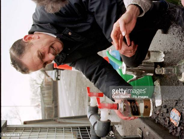 Bernard Boyle fills up a whisky bottle at a water collection point at Giffnock near Glasgow one of the areas affected by burst water pipes following...
