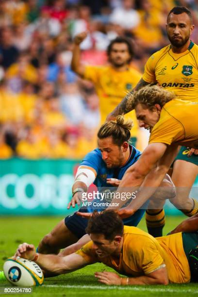 Bernard Foley of Australia beats the tackle of Michele Campagnaro to score a try during the international rugby match between Australia and Italy at...