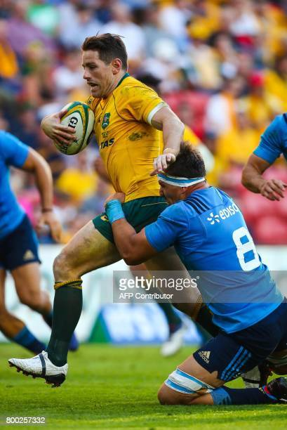 Bernard Foley of Australia is tackled by Andries Van Schalkwyk of Italy during the international rugby match between Australia and Italy at Suncorp...