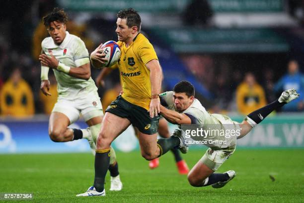 Bernard Foley of Australia runs with the ball as Ben Youngs holds on during the Old Mutual Wealth Series match between England and Australia at...