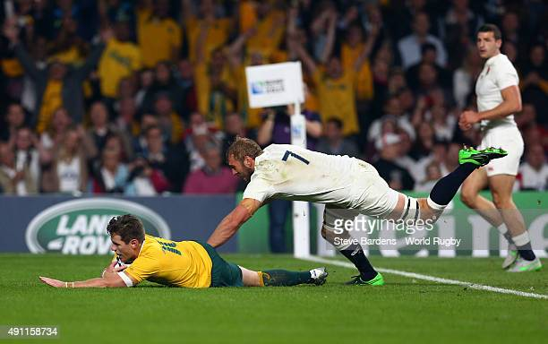 Bernard Foley of Australia scores his first try despite the tackle of Chris Robshaw of England during the 2015 Rugby World Cup Pool A match between...
