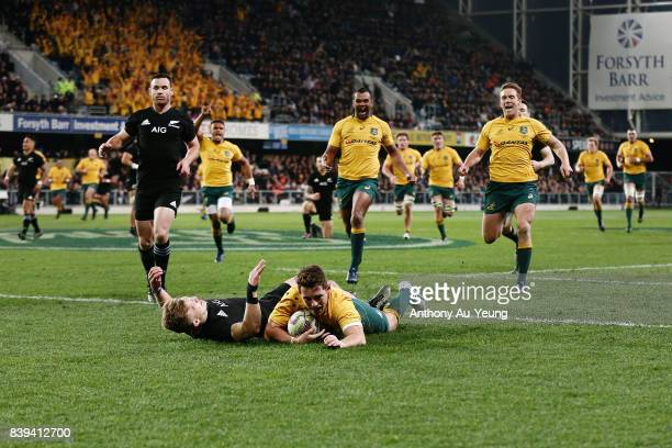 Bernard Foley of the Wallabies scores a try against Damian McKenzie of the All Blacks during The Rugby Championship Bledisloe Cup match between the...