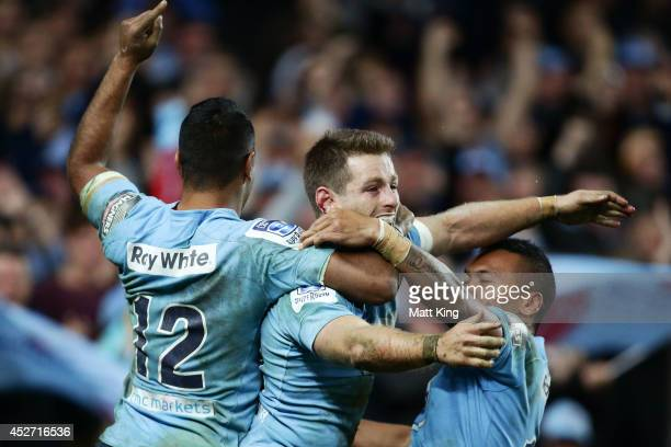 Bernard Foley of the Waratahs celebrates with Kurtley Beale and Alofa Alofa after scoring a try during the Super Rugby Semi Final match between the...