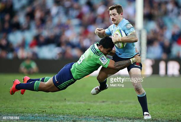 Bernard Foley of the Waratahs is tackled by Malakai Fekitoa of the Highlanders during the round 18 Super Rugby match between the Waratahs and the...
