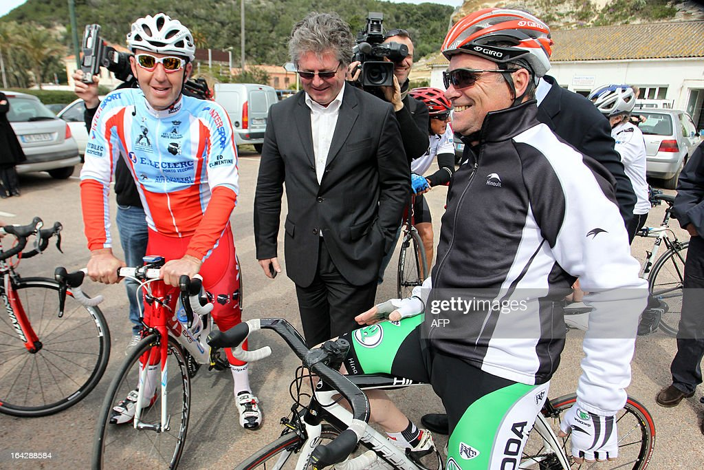 Bernard Hinault (R), French former cyclist champion and member of the directory board of the Tour de France cycling race, waits beside Georges Mela (C), Porto Vecchio mayor, before a 25 km ride on March 22, 2013 in Bonifacio, on the French Mediterranean island of Corsica, during an event to uncloak the countdown 100 days ahead of the race which will start from Porto-Vecchio, Corsica.