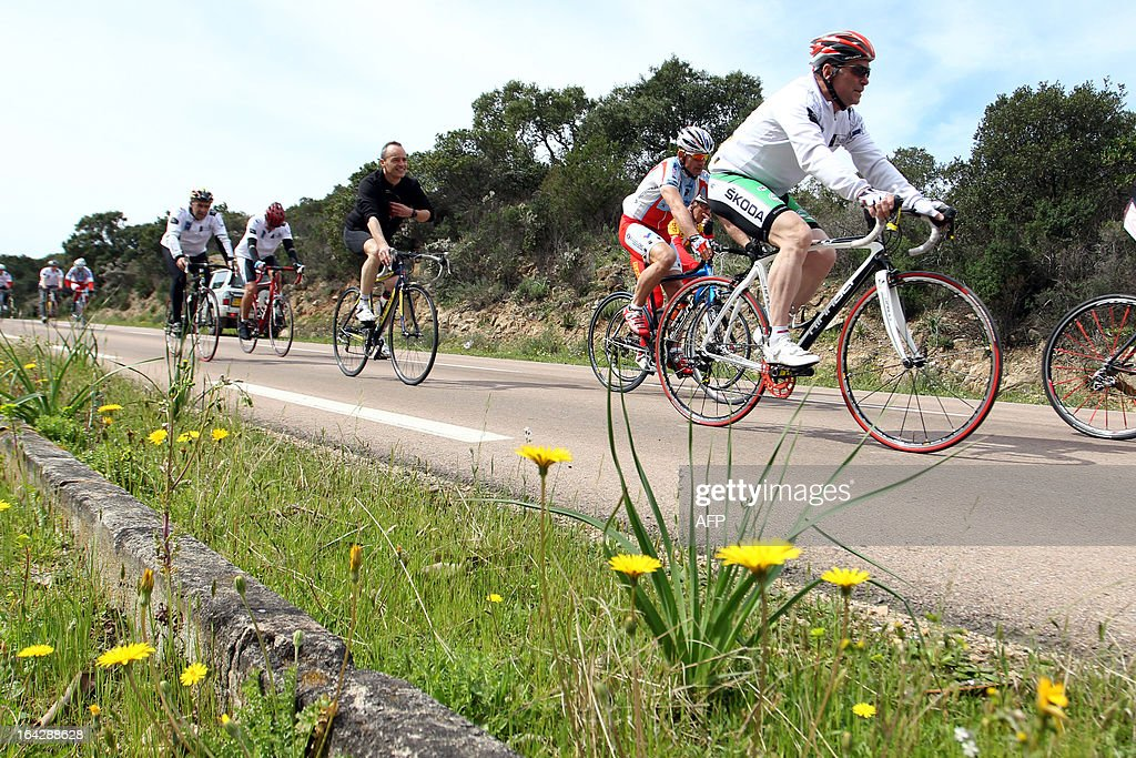 Bernard Hinault (R), French former cyclist champion and member of the directory board of the Tour de France cycling race, cycles a 25 km ride on March 22, 2013 in Bonifacio, on the French Mediterranean island of Corsica, during an event to uncloak the countdown 100 days ahead of the race which will start from Porto-Vecchio, Corsica.