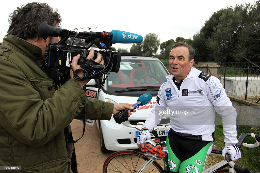 Bernard Hinault (R), French former cyclist champion and member of the directory board of the Tour de France cycling race, answers a journalist's questions after cycling a 25 km ride on March 22, 2013 in Bonifacio, on the French Mediterranean island of Corsica, during an event to uncloak the countdown 100 days ahead of the race which will start from Porto-Vecchio, Corsica.