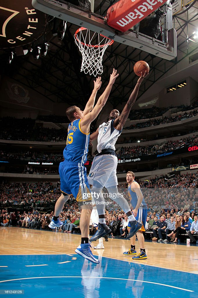 Bernard James #5 of the Dallas Mavericks looks to score against Andris Biedrins #15 of the Golden State Warriors on February 9, 2013 at the American Airlines Center in Dallas, Texas.