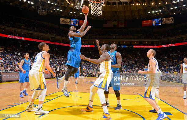 Bernard James of the Dallas Mavericks shoots a layup against the Golden State Warriors on March 11 2014 at Oracle Arena in Oakland California NOTE TO...
