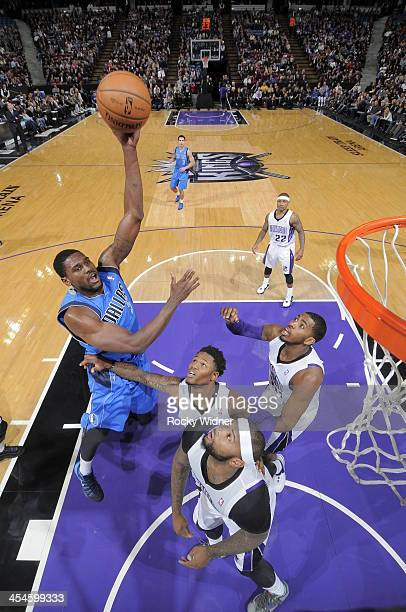 Bernard James of the Dallas Mavericks shoots the ball against Ben McLemore and DeMarcus Cousins of the Sacramento Kings at Sleep Train Arena on...
