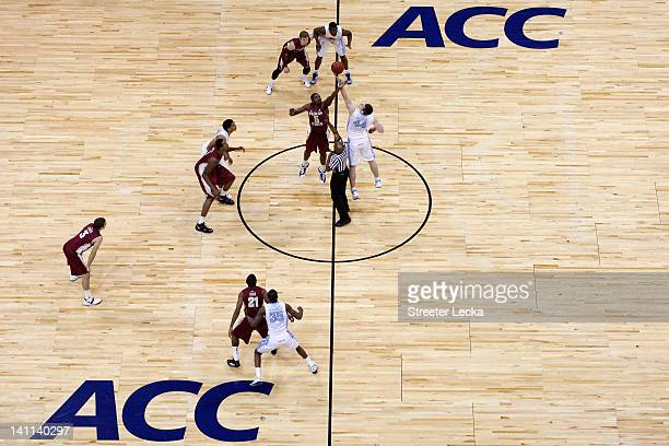 Bernard James of the Florida State Seminoles fights for control of the opening tipoff against Tyler Zeller of the North Carolina Tar Heels during the...