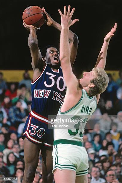 Bernard King of the New York Knicks goes up for a shot against Larry Bird of the Boston Celtics during a game played in 1983 at the Boston Garden in...