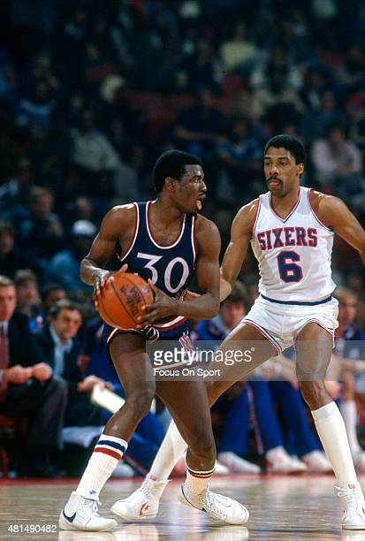 Bernard King of the New York Knicks looks to put a move on Julius Erving of the Philadelphia 76ers during an NBA basketball game circa 1983 at The...