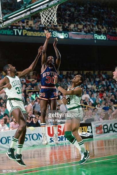 Bernard King of the New York Knicks shoots against Dennis Johnson and Cedric Maxwell of the Boston Celtics during a game played in 1984 at the Boston...