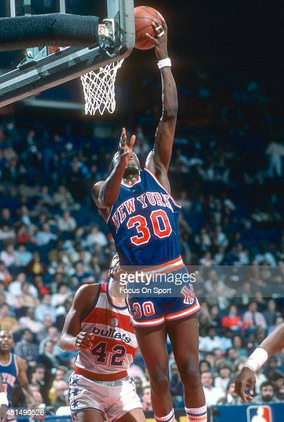 Bernard King of the New York Knicks shoots over Greg Ballard of the Washington Bullets during an NBA basketball game circa 1985 at the Capital Centre...