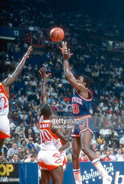 Bernard King of the New York Knicks shoots over Stewart Granger of the Atlanta Hawks during an NBA basketball game circa 1984 at the Omni Coliseum in...
