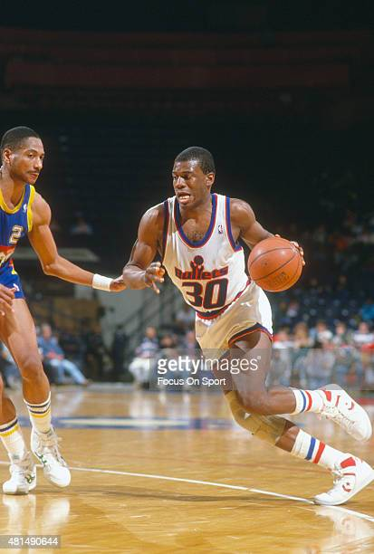 Bernard King of the Washington Bullets drives on Alex English of the Denver Nuggets during an NBA basketball game circa 1990 at the Capital Centre in...