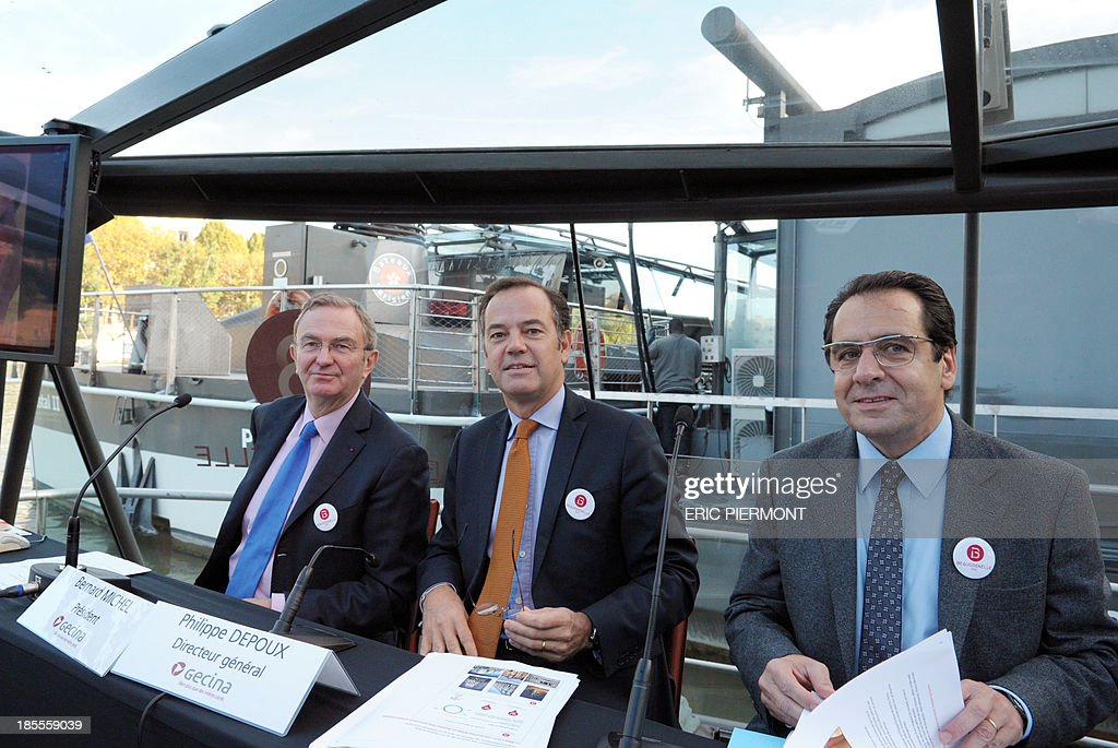 Bernard Michel, Chairman of French real estate investment trust Gecina, Philippe Depoux, Gecina CEO and Maurice Bansay, founder and Chairman of global operator in commercial real estate Apsys group pose aboard a boat on the Seine river prior to a press conference for the inauguration of the Beaugrenelle shopping center in Paris on october 22, 2013.