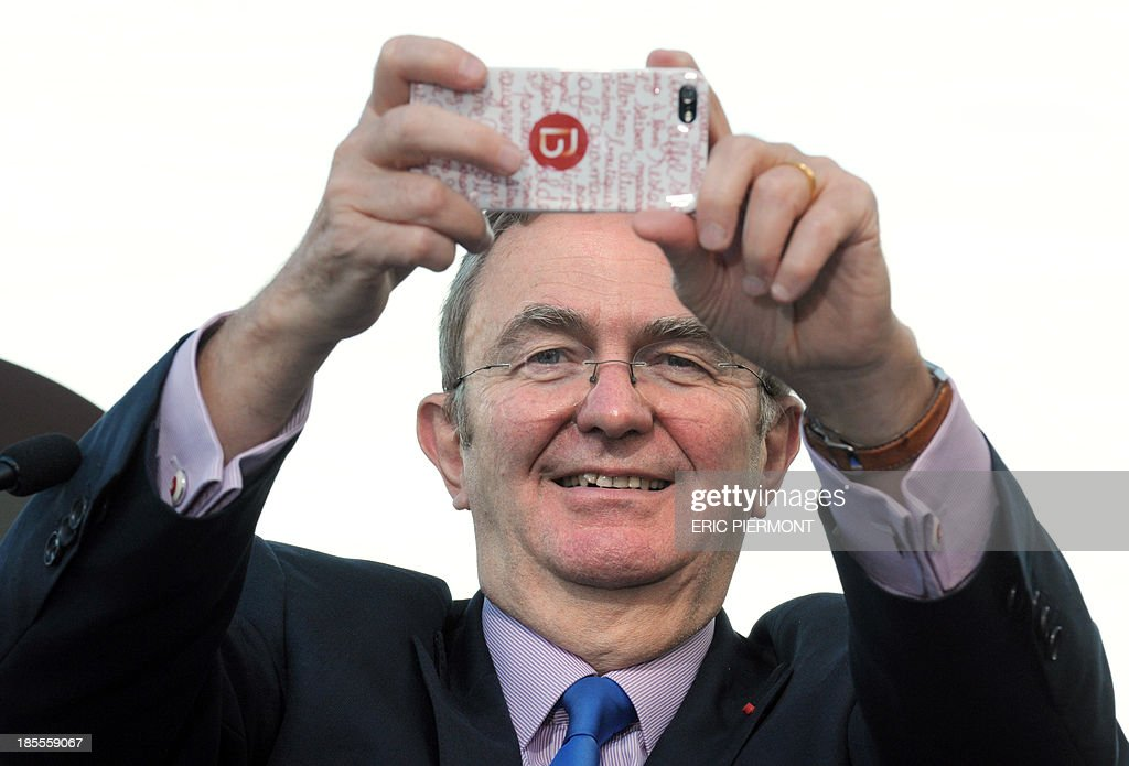 Bernard Michel, Chairman of French real estate investment trust Gecina takes a picture aboard a boat on the Seine river during a press conference for the inauguration of the Beaugrenelle shopping center in Paris on october 22, 2013.
