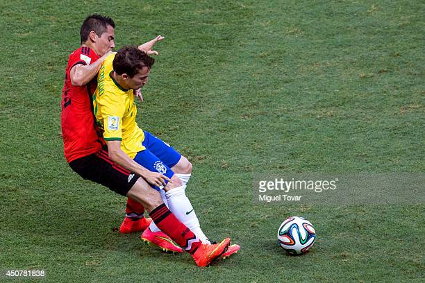 Bernard of Brazil figths off Paul Aguilar of Mexico during the 2014 FIFA World Cup Brazil Group A match between Brazil and Mexico at Castelao on June...