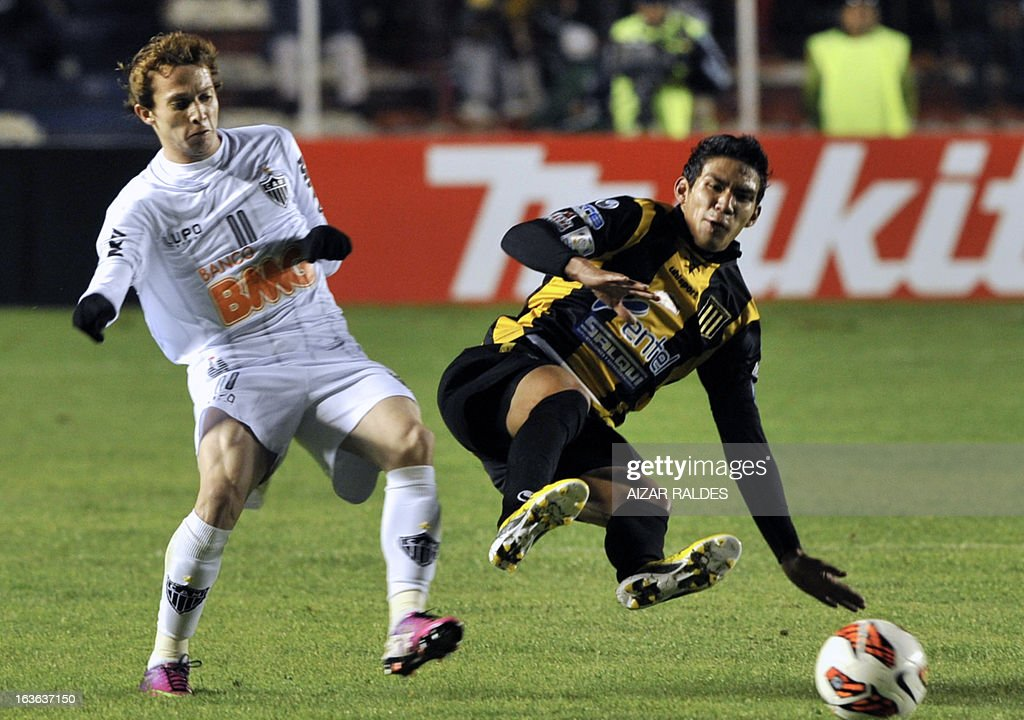 Bernard (L) of Brazil's Atletico Mineiro vies for the ball with Diego Bejarano of Bolivia's The Strongest during their Copa Libertadores football match at Hernando Siles stadium in La Paz, Bolivia, on March 13, 2013. AFP PHOTO/Aizar Raldes