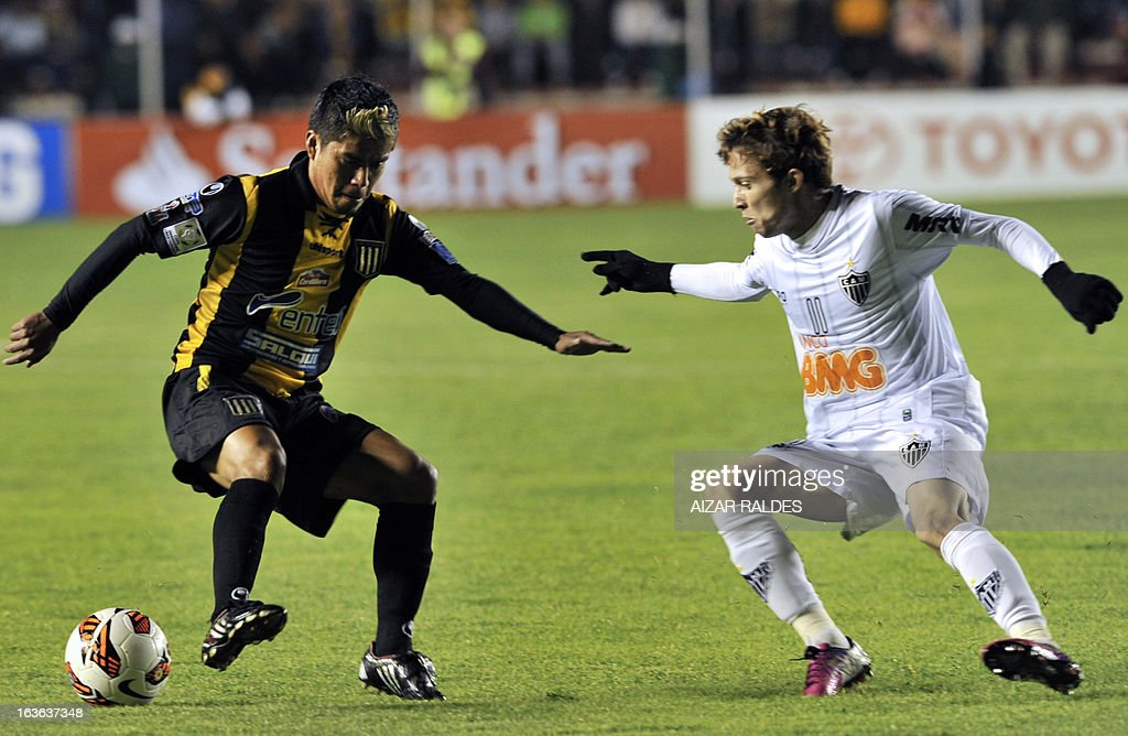 Bernard (R) of Brazil's Atletico Mineiro vies for the ball withNelvin Soliz, of Bolivia's The Strongest during their Copa Libertadores football match at Hernando Siles stadium in La Paz, Bolivia, on March 13, 2013. AFP PHOTO/Aizar Raldes